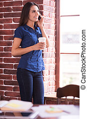 Good talk and cup of fresh coffee. Cheerful young woman talking on the mobile phone and holding cup of hot drink while standing near the window
