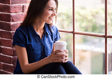 Lost in nice thoughts Cheerful young woman holding cup of...