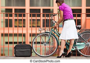 woman locking padlock - rear view of business woman locking...