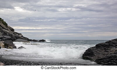 Beach on the Ligurian Sea early in the morning in cloudy...