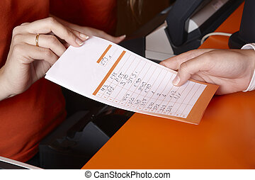 Bet ticket with male and female hands. Horizontal