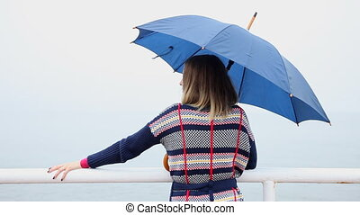 Woman with umbrella on pier. Sea.