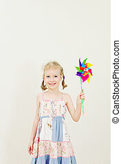 Little girl with colorful pinwheel. Vintage effect.