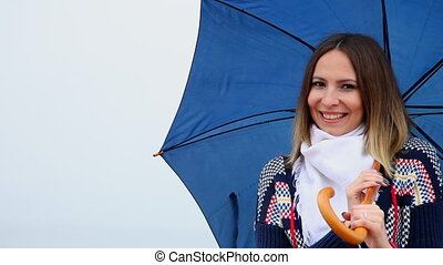 Woman with blue umbrella winking - Smiling young woman with...