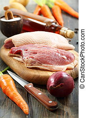 Raw duck breast and vegetables - Duck breast on a cutting...