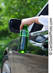Driving Under the Influence Female hand with bottle of beer...