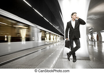 young businessman with phone in the subway - A young...