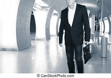 business man walking in subway - a young businessman is...
