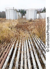 Old rusty pipes and tanks at an abandoned oil refinery