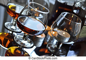 Brandy in a glass - a glass of brandy and a candle,...