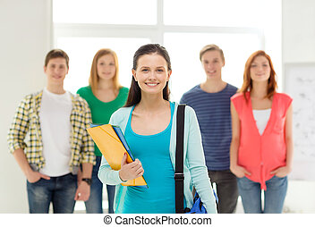 smiling students with teenage girl in front - education and...