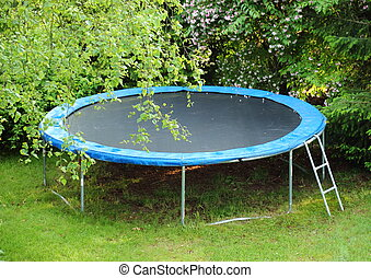 Blue trampoline on the lawn in garden