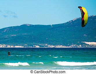 Kite surfing on a pristine beach - young sportsman kite...