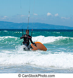 Kite surfing on a pristine beach - kite sergfer on clean...