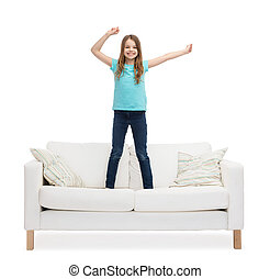 smiling little girl jumping or dancing on sofa - home,...