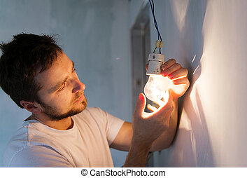 Electrician working - Electrician installing light in a new...