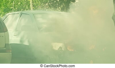 Car engulfed in flames with lot of smoke A man tries to...