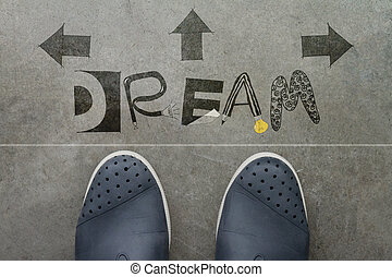 Hand drawn DREAM  design word on front of business man feet as c