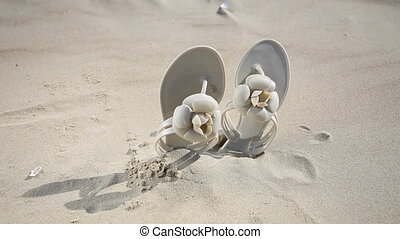 Flip flops on the sandy beach Sea - Beige female flip-flops...