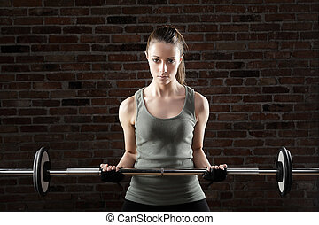 Sexy fit woman lifting dumbbells on brick background -...