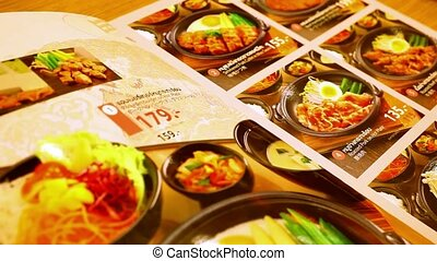 Flipped Japanese restaurant menu and a selection of dishes. Macro video