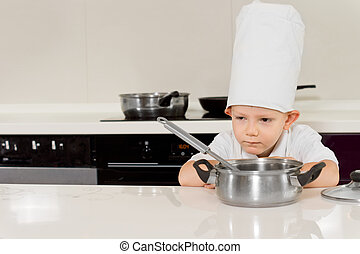 Little boy cooking bending down to smell the food - Little...