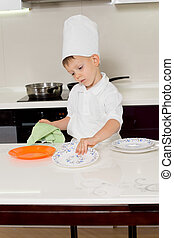 Cute little boy chef getting ready for dinner