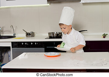 Small little boy in a chefs uniform wiping dishes