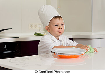 Cute little chef cleaning the kitchen counter