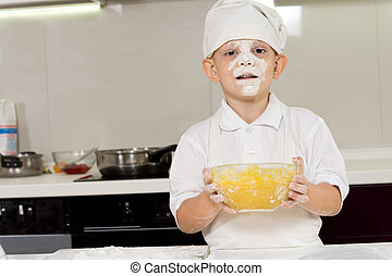 Cute young chef with a face full of flour - Cute young boy...