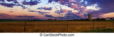 Landscape with a field and silo under a colorful cloudy sky