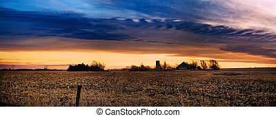 Landscape with a field and farm under a colorful cloudy sky