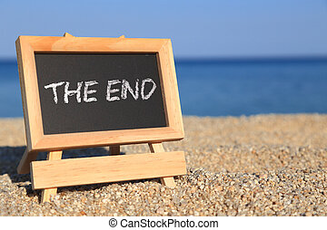 """Blackboard with """"The end"""" text on the beach"""