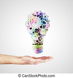 hand holding light bulb with color gears