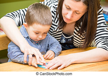 Mother and child boy drawing together with color pencils in...