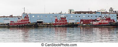 Three Red Tugboats Paroramic - Red Tugboats tied up in a...