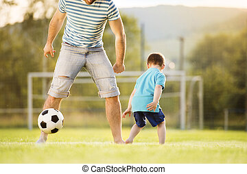 Father and son playing football - Young father with his...