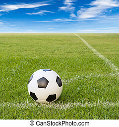 soccer ball on soccer field against blue sky background