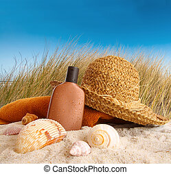 Straw hat with towel at the beach