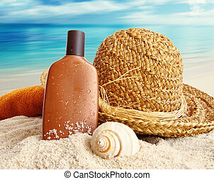 Straw hat with towel and lotion on the beach