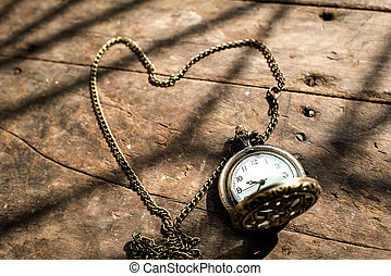 heart pocket watch on a wood background with natural light