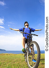 close-up man sitting on a mountain bike and open arms to...