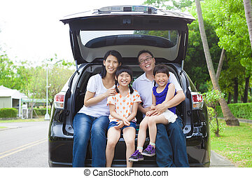 happy family sitting in the car and their house behind