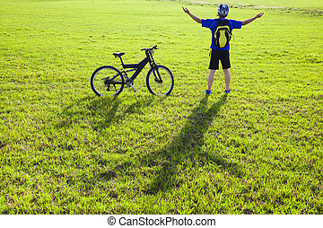 young backpacker relaxing on a meadow with bicycle