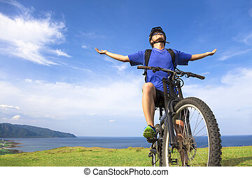 young man sitting on a mountain bike and open arms to...