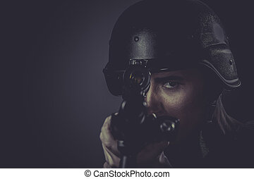 Police, paintball sport player wearing protective helmet aiming