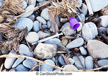 Used syringe on pebbles - Used syringe and plants washed out...