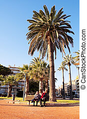 Couple in Antibes - An elderly couple sitting on a bench in...