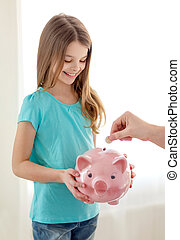 smiling little girl holding piggy bank - education, family,...