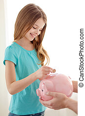 smiling little girl putting coin into piggy bank -...